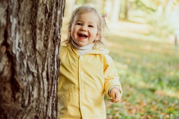 Kaukasisches kindermädchen lachend, das im park nahe einem baum geht. Premium Fotos