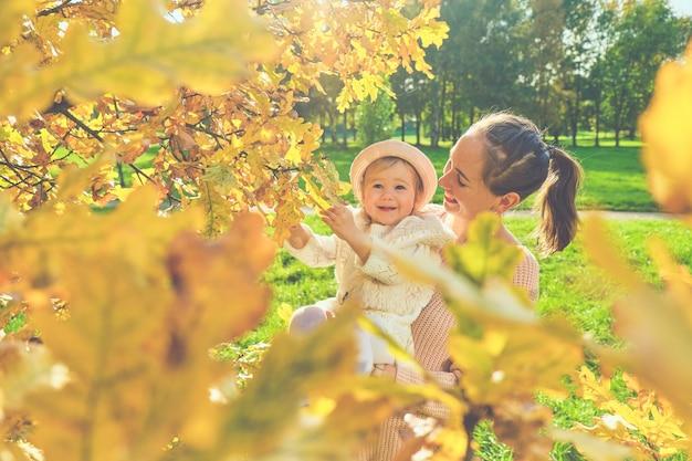 Kaukasisches kindermädchen mit mutter nahe einem baum freudig im herbstpark. Premium Fotos