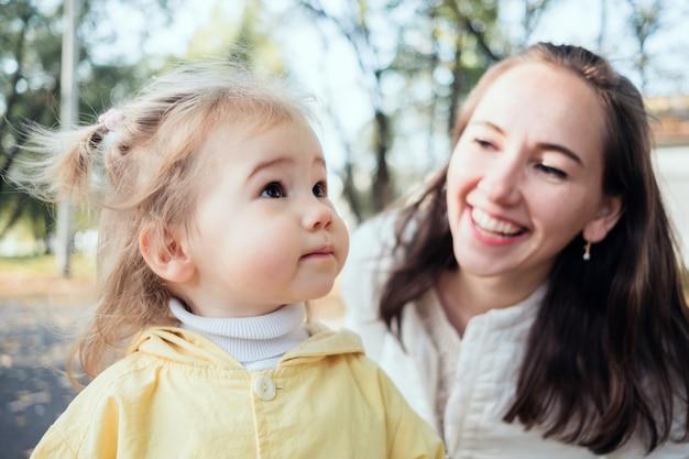 Kaukasisches kindermädchen- und mutterporträt, das im park lächelt. Premium Fotos