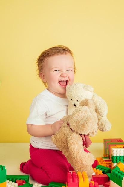 Kaukasisches kleines mädchen, kinder lokalisiert auf gelbem studiohintergrund. porträt des niedlichen und entzückenden kindes, des babys, das spielt und lacht. Kostenlose Fotos
