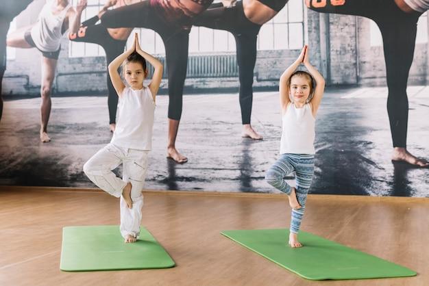 Kaukasisches kleines mädchen zwei, das auf yogamatte über holzoberfläche übt Kostenlose Fotos