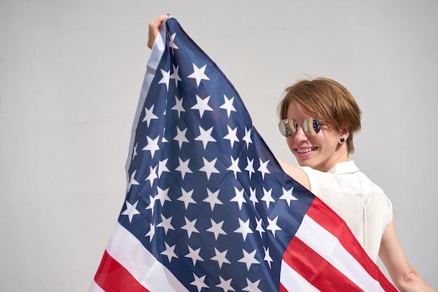 Kaukasisches lächelndes mädchen der rothaarigen hält usa-flagge hinter ihr zurück Premium Fotos