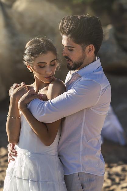 Kaukasisches liebespaar, das weiße kleidung trägt und im strand während eines hochzeitsfotoshootings umarmt Kostenlose Fotos