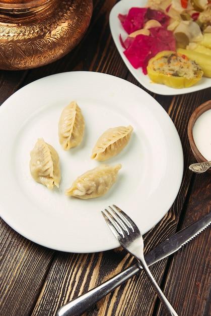 Kaukasisches traditionelles essen, khinkali, dushbere, gurze, serviert mit turshu. Kostenlose Fotos