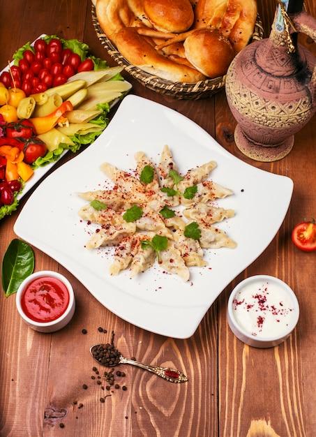 Kaukasisches traditionelles foodl dushbere, gurze diente mit joghurt und tomatensauce. in weißen teller mit turshu auf holztisch dekoriert Kostenlose Fotos