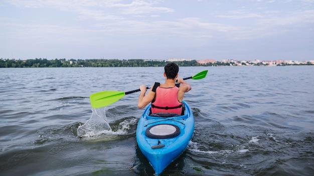 Kayaker, der wasser mit dem paddel beim kayak fahren spritzt Kostenlose Fotos