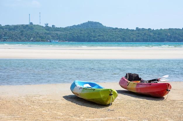 Kayaking auf dem sand der seehintergrundberge und -felsen. Premium Fotos
