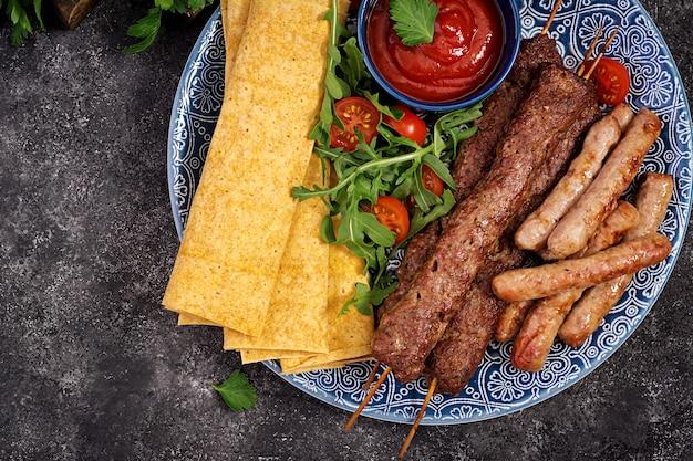 Kebab adana, lamm und rindfleisch auf lavashbrot mit tomatensauce Premium Fotos