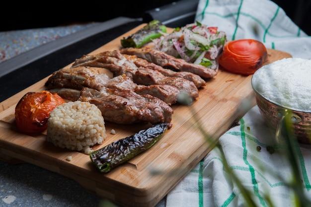 Kebab-rippen von der seite mit gebratenem gemüse und gehackten zwiebeln und ayran und messer im schneidebrett Kostenlose Fotos