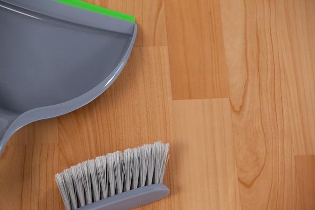 Kehrschaufel und ausgedehnte bürste auf bretterboden Premium Fotos