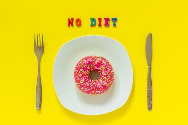 Keine diät und rosa donut auf weißer platte und messergabel auf gelbem hintergrund. Premium Fotos