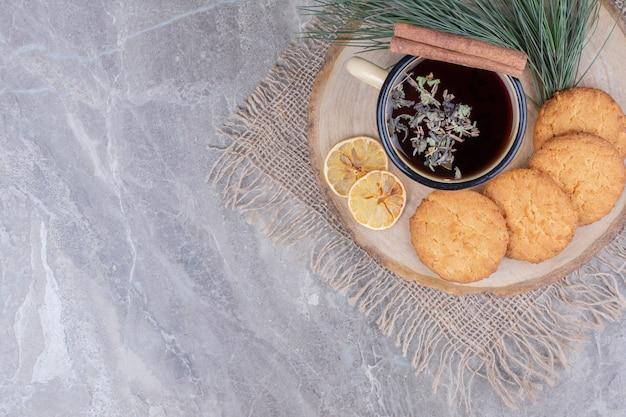 Kekse auf einer holzplatte mit einer tasse glitzern und zitronenscheiben Kostenlose Fotos