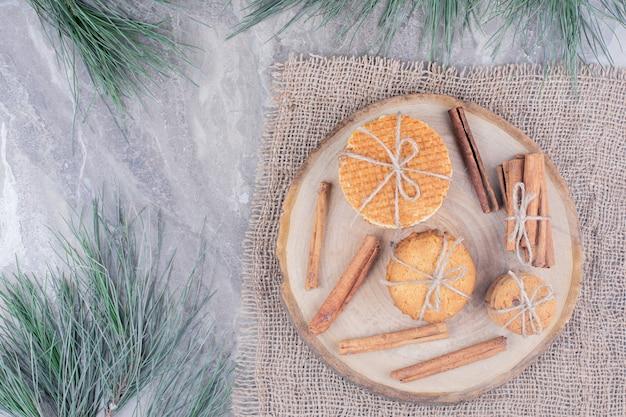 Kekse auf einer holzplatte mit zimtstangen herum Kostenlose Fotos