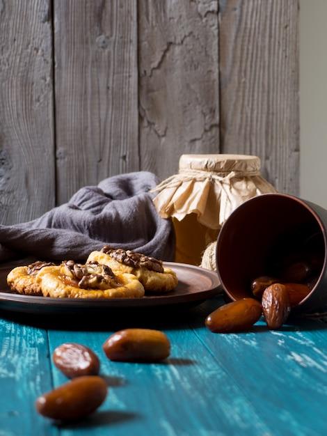 Kekse, ein glas honig und verstreute datteln auf türkisfarbenem holz Premium Fotos