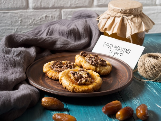 Kekse, honig und datteln mit einer weißen karte für die inschrift. Premium Fotos