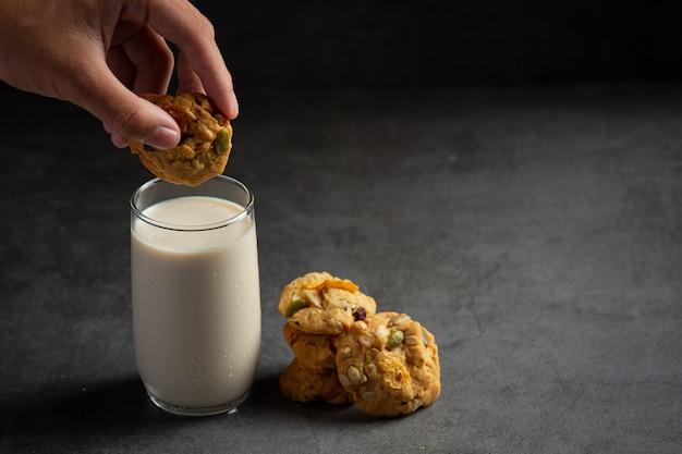 Kekse mit einem glas milch auf dunklem boden serviert Kostenlose Fotos