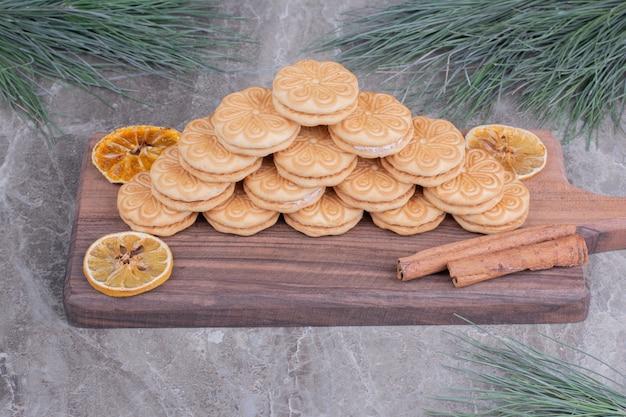 Kekse mit zimtstangen und trockenen zitronenscheiben auf einem holzbrett Kostenlose Fotos