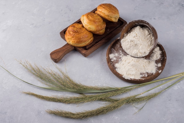 Kekse oder brötchen mit mehl auf einer holzplatte mit gewürzen serviert Kostenlose Fotos
