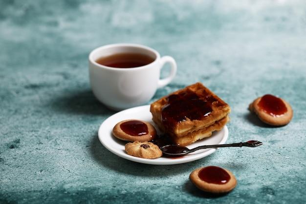Kekse und eine weiße tasse tee. Kostenlose Fotos