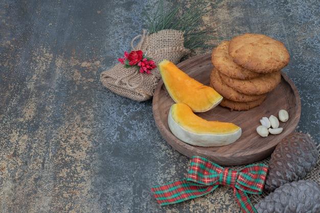 Kekse und kürbisscheiben auf holzteller mit band verziert. hochwertiges foto Kostenlose Fotos