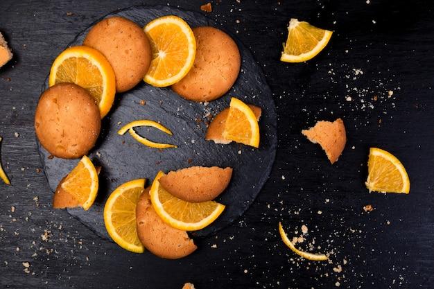 Kekse und orangenfrucht auf schieferteller auf schwarzer unterlage, Premium Fotos