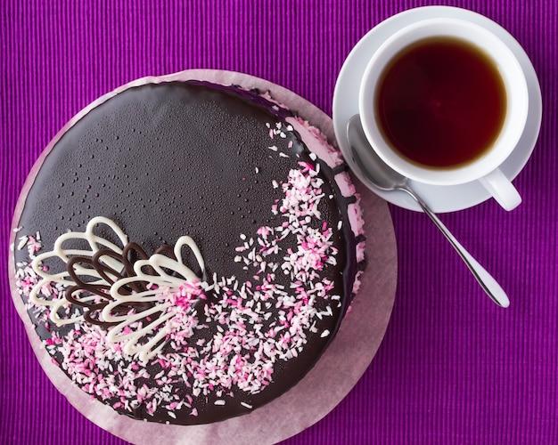 Kekskuchen mit fruchtsouffle, dekoriert mit schokolade und einer tasse tee. draufsicht Premium Fotos