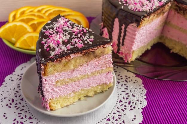 Kekskuchen mit fruchtsouffle, dekoriert mit schokolade und einer tasse tee. stück kuchen ist isoliert. Premium Fotos