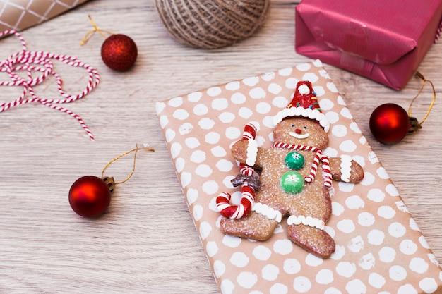 Keksschneemann auf geschenk nahe weihnachtsbällen Kostenlose Fotos