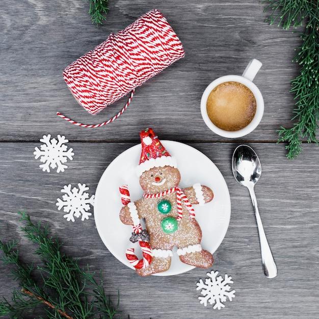 Keksschneemann auf platte nahe schale des getränks, der schneeflocken und der threads Kostenlose Fotos