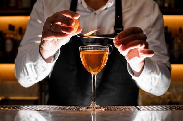 Kellner, der ein frisches alkoholisches cocktail mit rauchiger anmerkung macht Premium Fotos