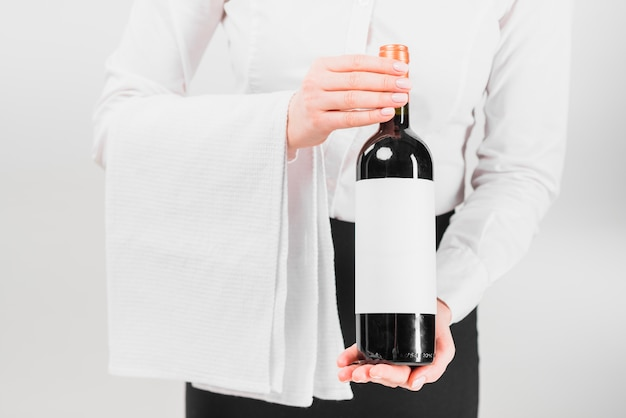 Kellner, der flasche wein hält und anbietet Kostenlose Fotos