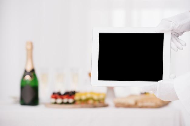 Kellner, der tablette mit modell hält Kostenlose Fotos