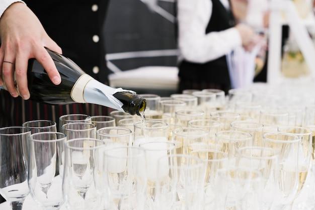 Kellner gießt champagner in gläser Kostenlose Fotos