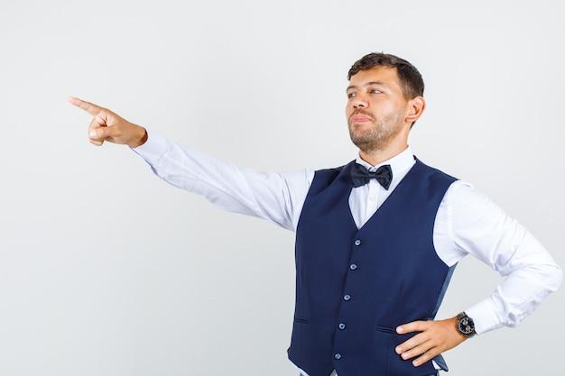 Kellner im hemd, weste zeigt finger zur seite mit der hand auf der taille und sieht selbstbewusst aus, vorderansicht. Kostenlose Fotos