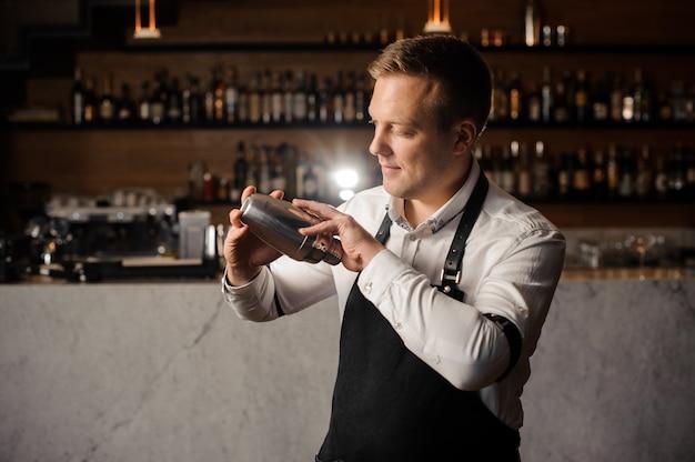 Kellner in einem weißen hemd und in einem schutzblech, die einen schüttel-apparat gegen den stangenzähler halten Premium Fotos