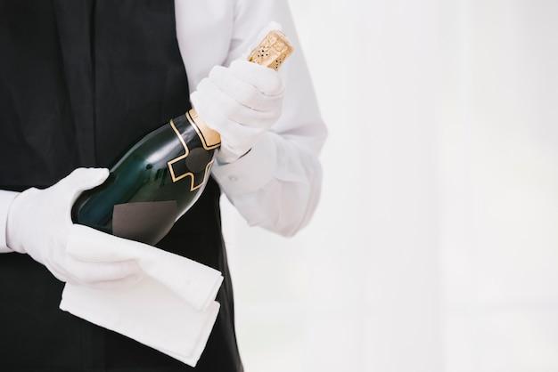 Kellner in uniform präsentiert champagner Kostenlose Fotos