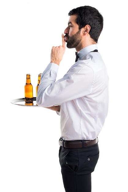Kellner mit bierflaschen auf dem tablett machen stille geste Kostenlose Fotos