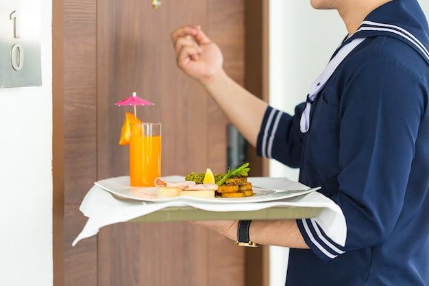 Kellnerhalteplatte mit frühstück und klopftür vor einem hotelzimmer. Premium Fotos