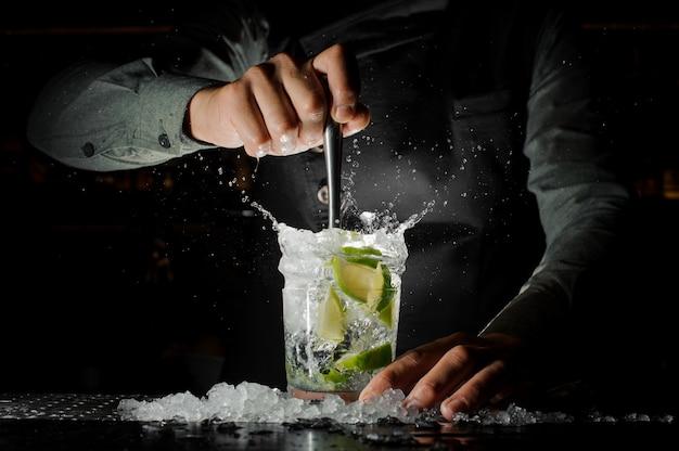 Kellnerhand, die frischen saft vom kalk macht den caipirinha-cocktail zusammendrückt Premium Fotos