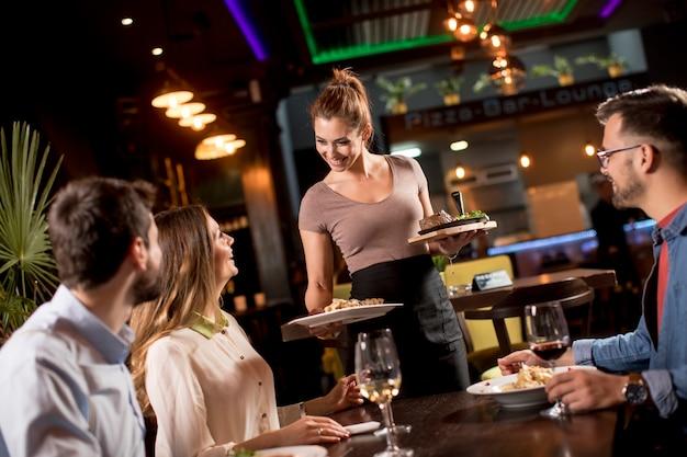 Kellnerin, die gruppe von freunden mit essen im restaurant dient Premium Fotos