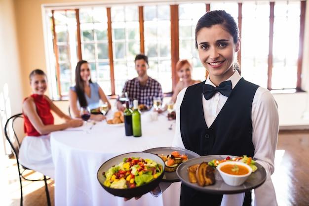 Kellnerin, die lebensmittel auf platte im restaurant hält Premium Fotos