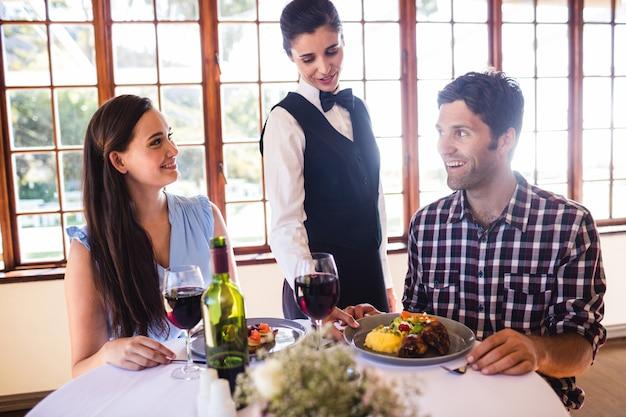 Kellnerin, die lebensmittelplatte auf kundentabelle dient Premium Fotos