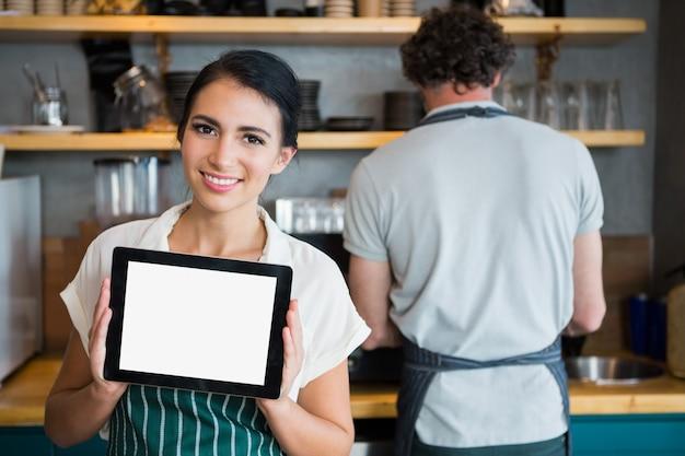 Kellnerin hält digitales tablett, während kellner im hintergrund arbeitet Premium Fotos