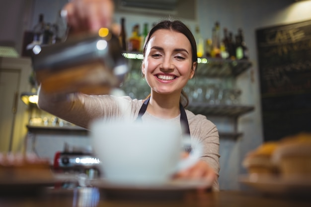 Kellnerin macht tasse kaffee an der theke im café ...