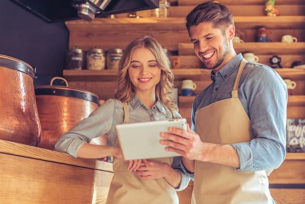 Kellnerin und junger kellner in den schutzblechen benutzen eine tablette. Premium Fotos