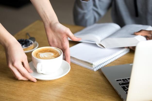 Kellnerumhüllungscappuccino zum cafeteriabesucher am cafétisch, nahaufnahme Kostenlose Fotos