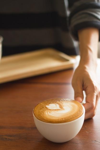 Kellnerumhüllungskaffee auf schlechter beleuchtung fokussiert an der kaffeetasse. Premium Fotos
