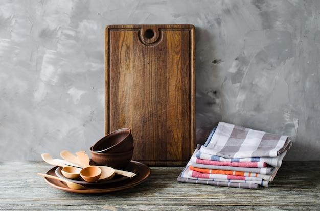 Keramikplatten, holz- oder bambusbesteck, vintage-schneidebrett und handtücher im innenraum der küche. Premium Fotos