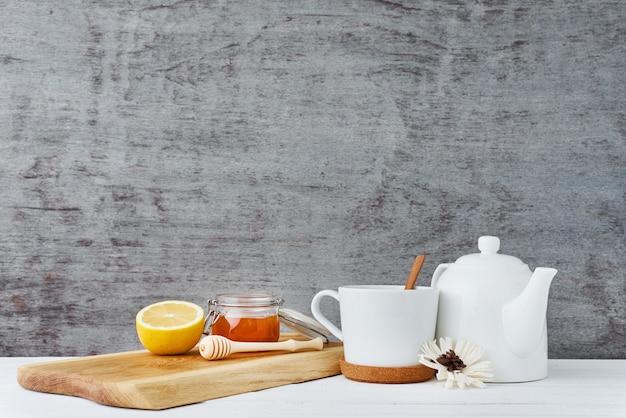 Keramische teekanne, weiße schale, honig in einem glasgefäß und zitrone auf hölzernem Premium Fotos