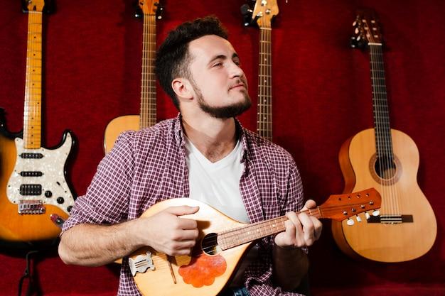 Kerl, der an der mandolinengitarre im studio spielt Kostenlose Fotos